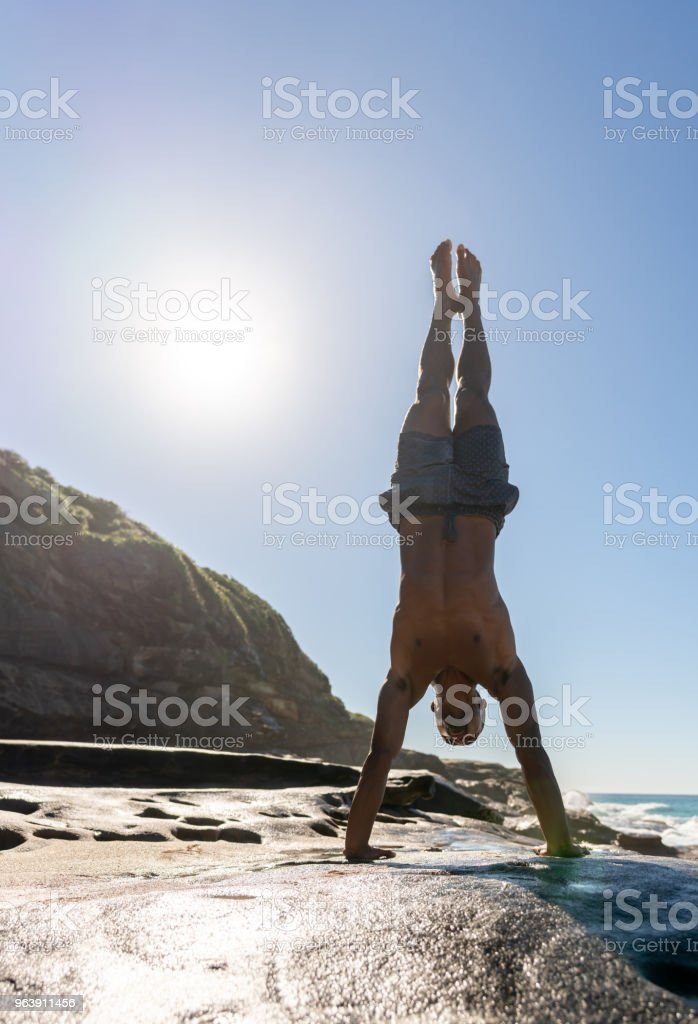 Athletic man doing yoga exercises at the beach - Royalty-free Adult Stock Photo