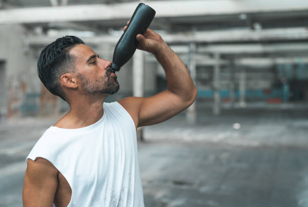 Athletic Man Drinking Water after Exercising in a Warehouse stock photo