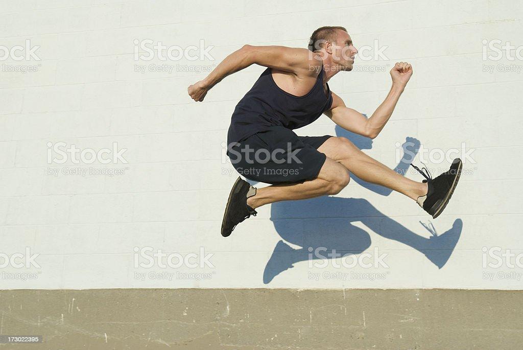Athletic Man Hurdles Against White Wall royalty-free stock photo