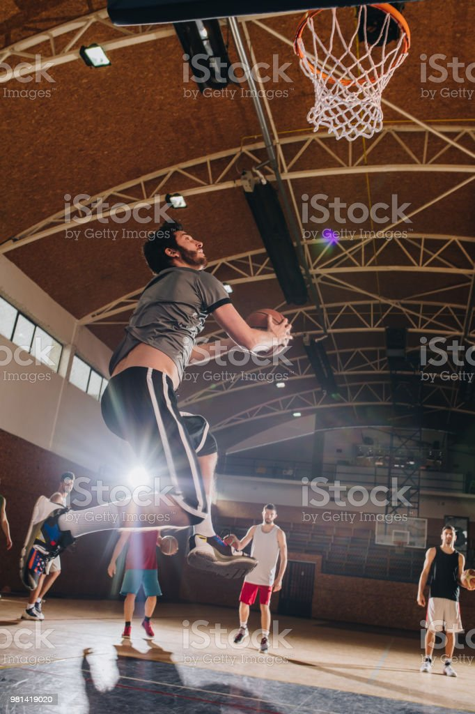 Basketball player exercising jump shoots during a sports training on...