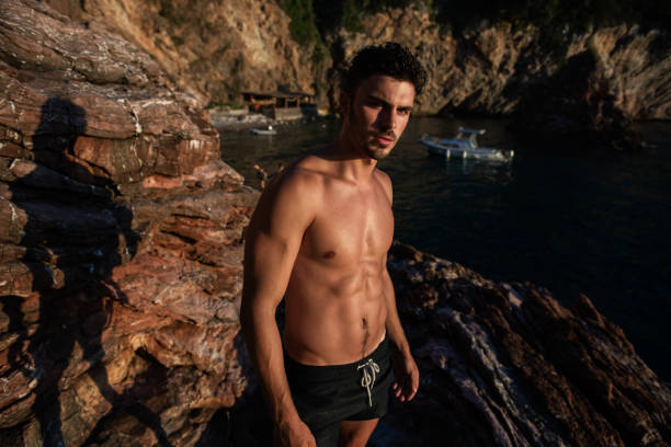 Athletic man in the sea  by rocks stock photo