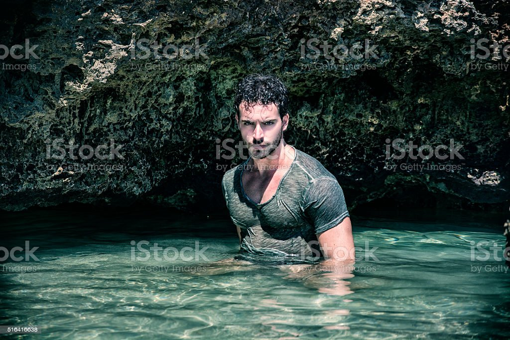 Athletic man in the sea or ocean by rocks, wet stock photo