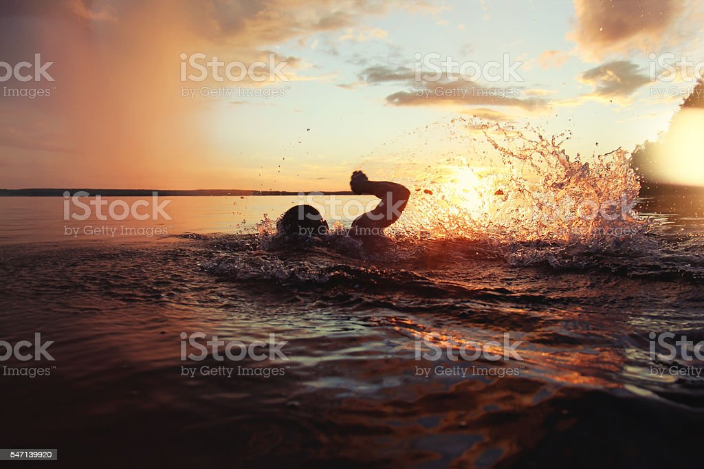 Athletic man is trained to swim in lake at sunset – Foto