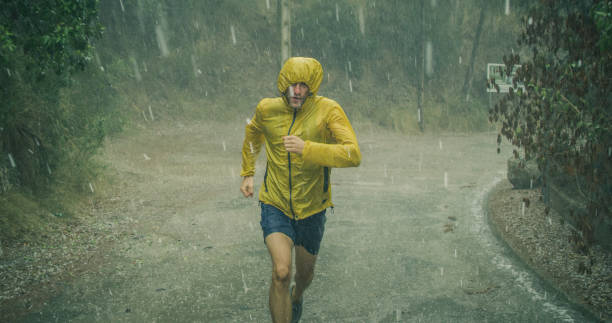 Athletic man jogging in extreme weather condition. Hail and rain stock photo