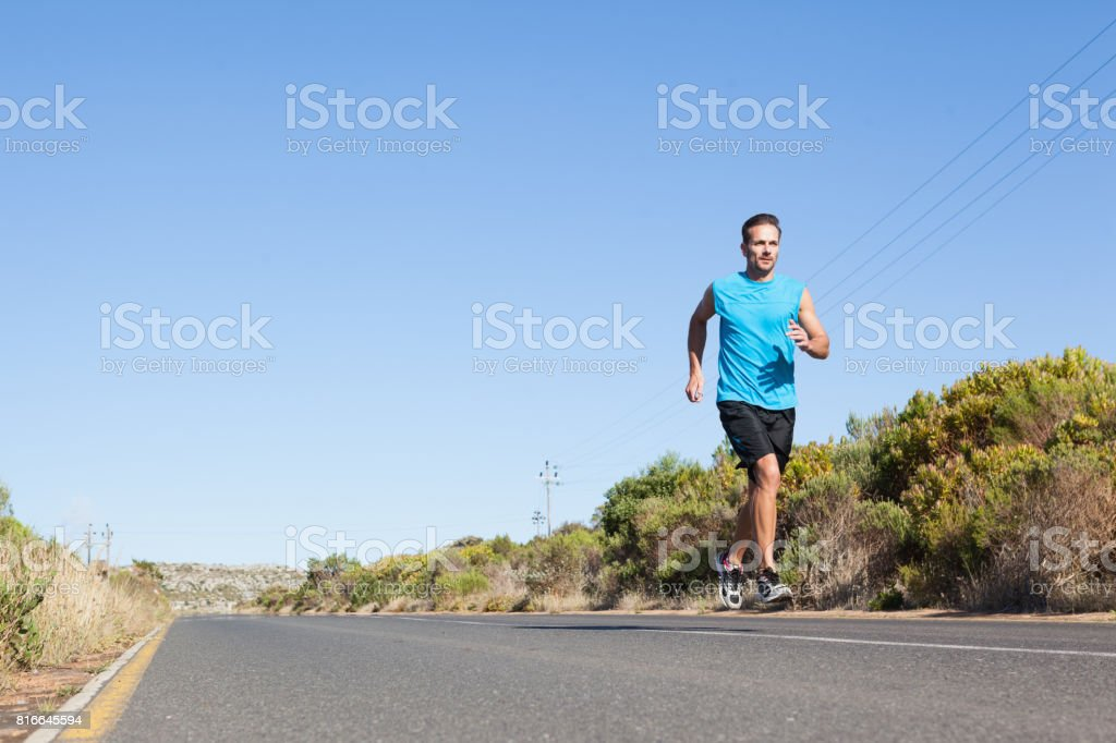 Athletic man jogging on the open road stock photo