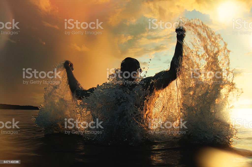 Athletic man jumps out of the water at sunset stock photo