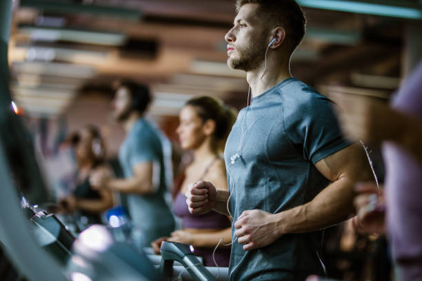 Athletic man listening music while running on treadmill in a gym. stock photo