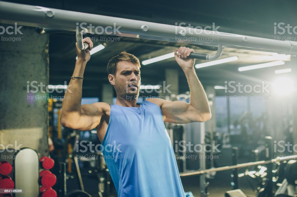 Athletic man making an effort while exercising chin-ups in a gym. royalty-free stock photo