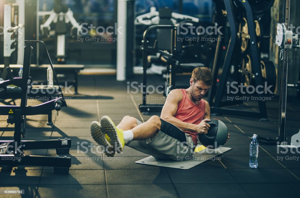 Young male athlete making an effort while doing sit-ups with medicine...