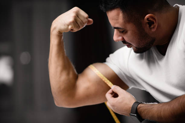 Athletic man measures his bicep with a measuring tape. Athletic man measures his bicep with a measuring tape. The concept of fitness and health bicep stock pictures, royalty-free photos & images