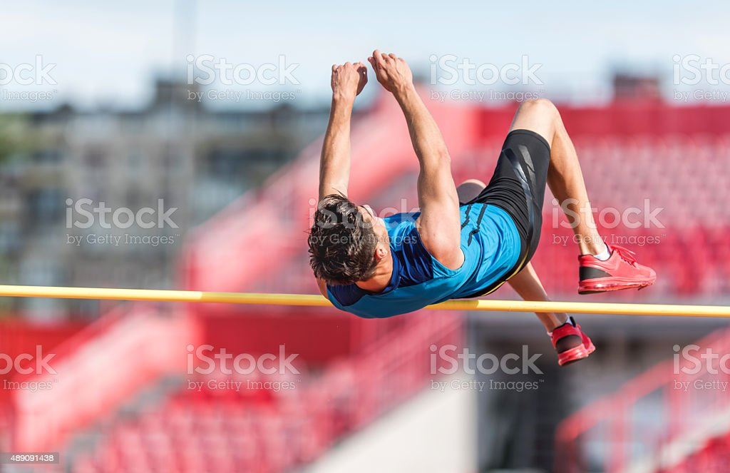 Athletic man performing high jump on a competition. stock photo