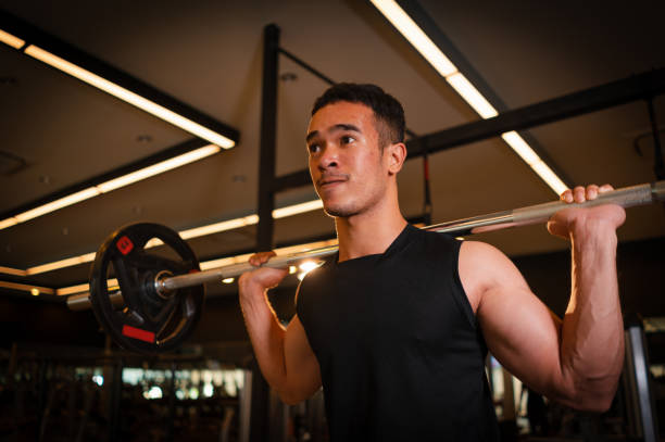 Athletic man playing dumbbell exercise for arm endurance training exercise to strengthen and tone the shoulder muscles. concept of weight training. stock photo