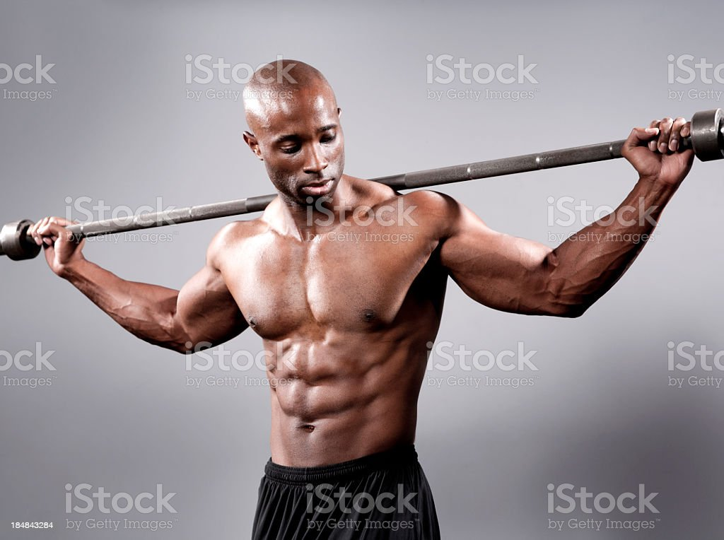 Athletic man posing with a barbell stock photo