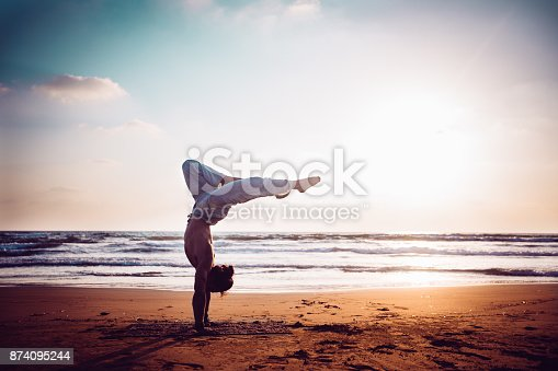 istock Athletic man practising yoga on the beach at sunset 874095244