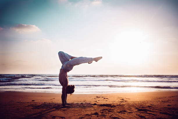Athletic man practising yoga on the beach at sunset stock photo