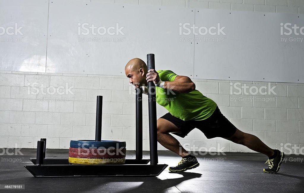 Athletic man pushing a gym sled stock photo