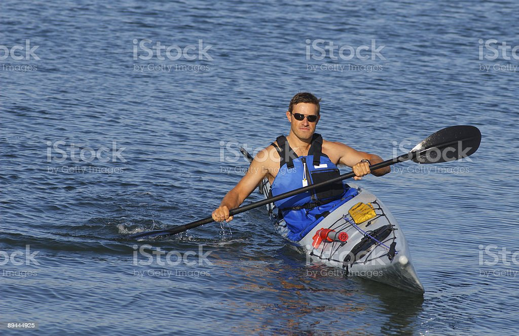 Athletic man rowing a kayak and looking proud royalty-free stock photo