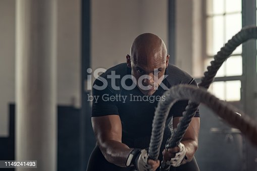 istock Athletic man using battle rope at gym 1149241493