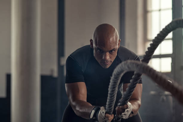 Athletic man using battle rope at gym Man in sportswear doing battle ropes functional training at cross training centre. Determined trainer making waves with ropes while exercising strength. Athlete working out with battle rope at industrial gym. effort stock pictures, royalty-free photos & images