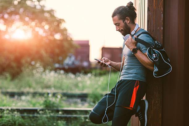 athletic man using his smart phone. - handytasche stock-fotos und bilder