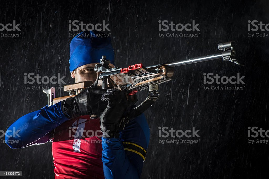 Athletic man with biathlon rifle stock photo