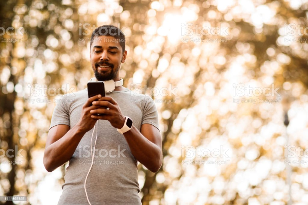 Young man with headphones around his neck typing a message on a...