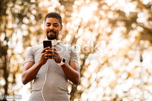 istock Athletic man with headphones around his neck typing a message on a smart phone 1144867357