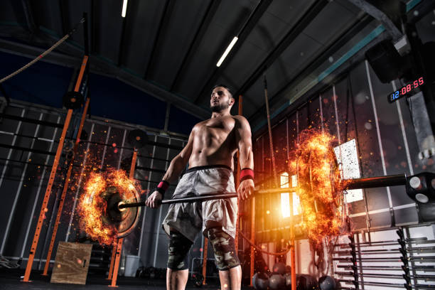 Athletic man works out at the gym with a fiery barbell - foto stock