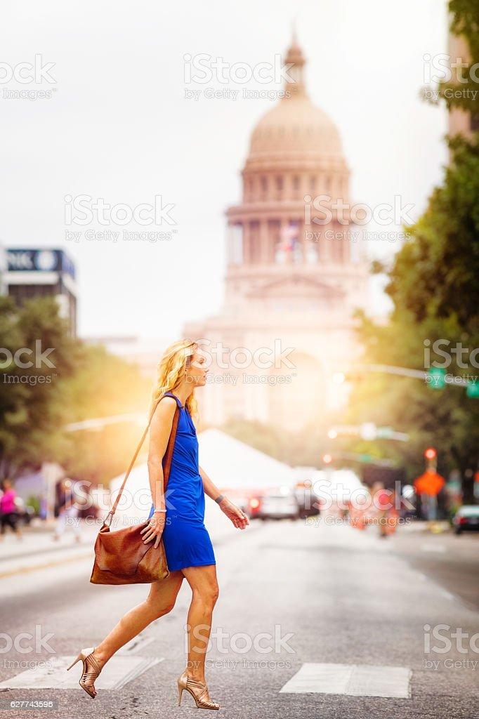 Athletic mature woman crossing Austin Congress street stock photo
