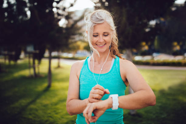 Athletic mature woman monitoring her running performance on smartwatch Fit senior woman listening to music and checking her pulse and jogging time on smartwatch woman taking pulse stock pictures, royalty-free photos & images
