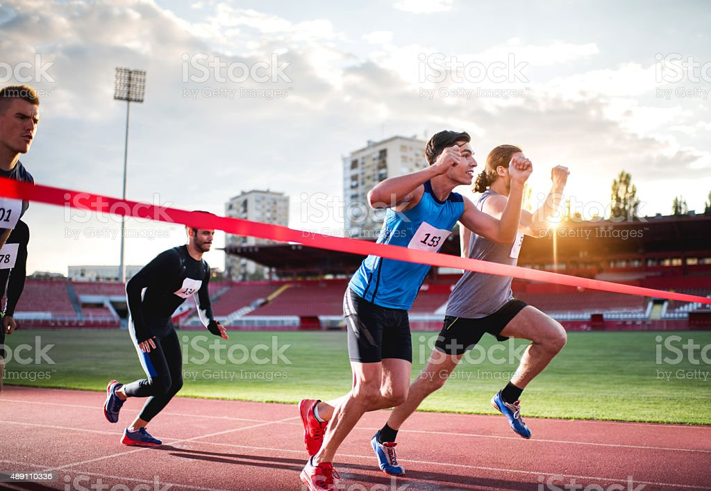 Athletic men about to cross the finish line . stock photo