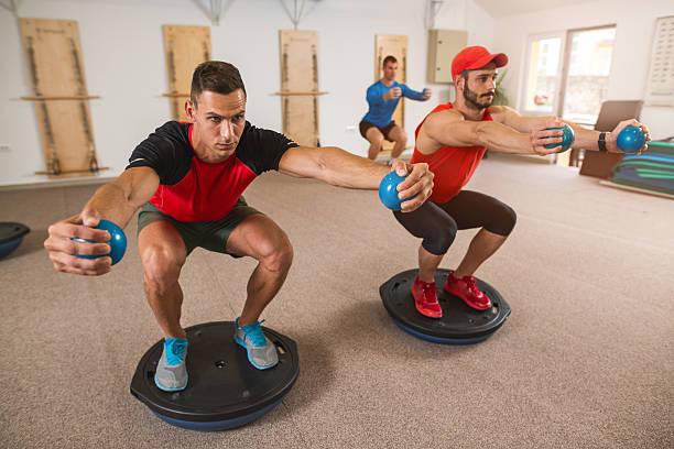 Athletic men doing squats on bosu ball in health club. stock photo