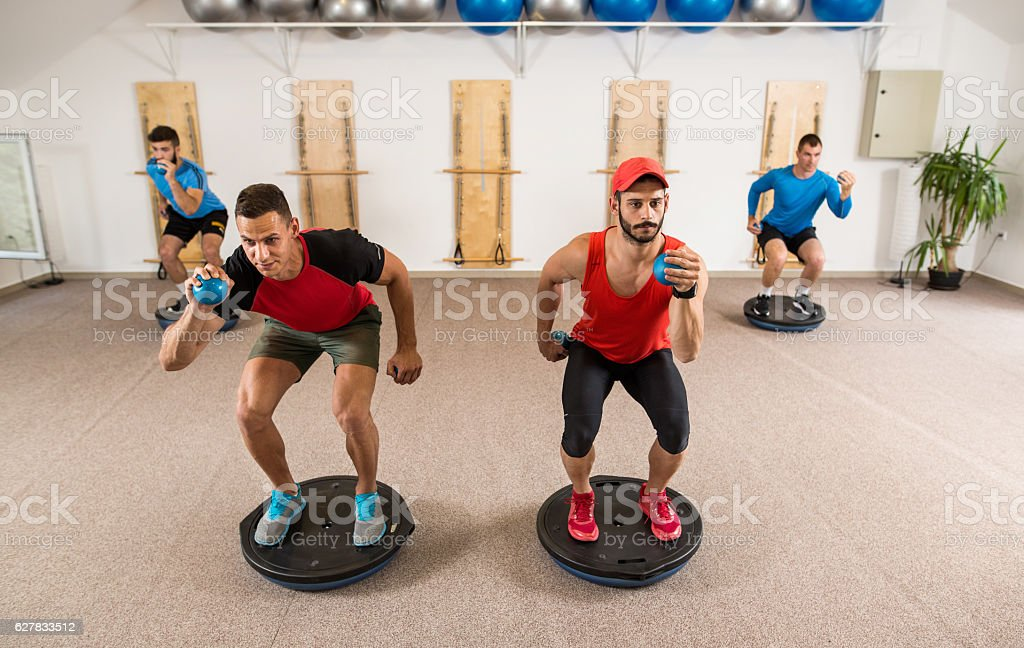 Athletic men exercising with weights while balancing on bosu balls. stock photo