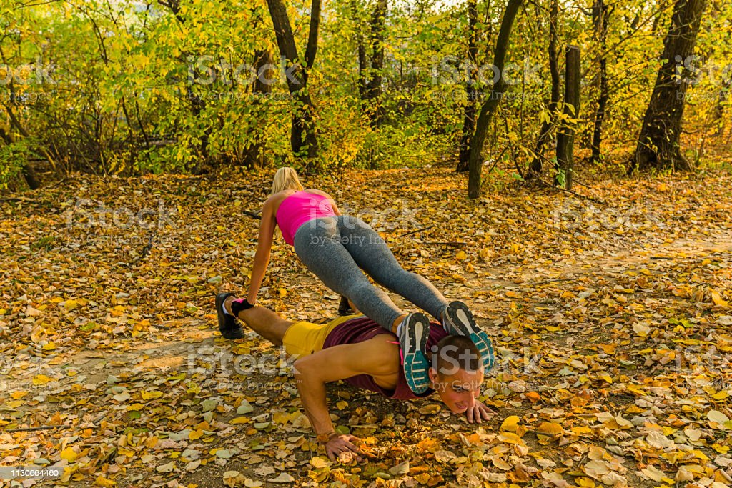 Beautiful Blonde Woman and Young Male Athlete Doing Push-ups Together...