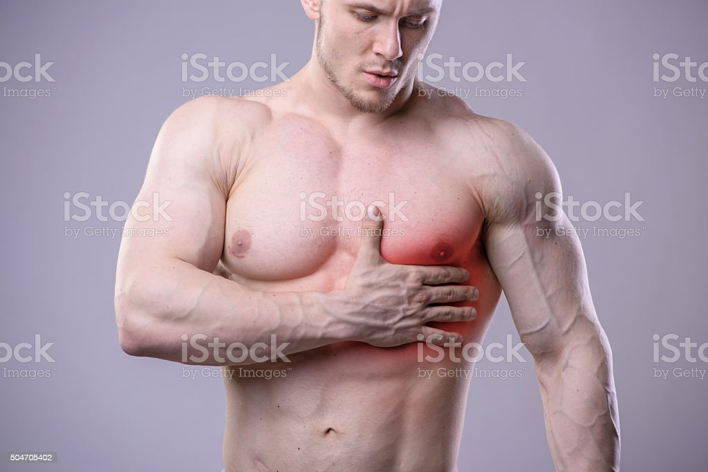 Athletic muscular man has pain in the heart. Red spot stock photo