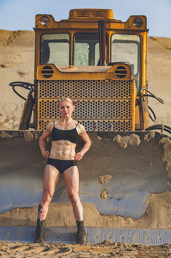 muscular woman in the background is the bulldozer