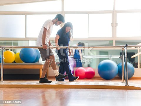 An athletic male patient walking in the parallel bars next to therapist.