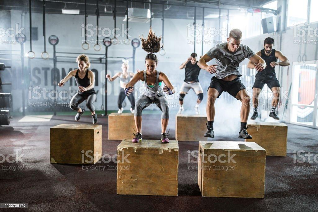Gente atlética saltando en cajas durante el entrenamiento cruzado en un club de salud - Foto de stock de Actividad física libre de derechos