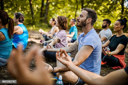 istock Athletic people practicing Yoga on a sports class in nature. 860080282