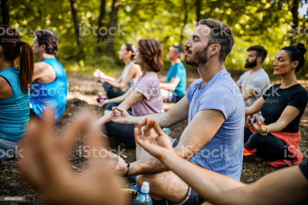Athletic people practicing Yoga on a sports class in nature. stock photo