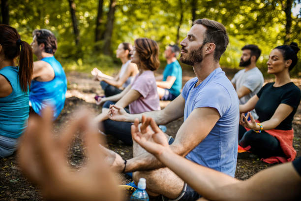 athletic people practicing yoga on a sports class in nature. - zen like stock pictures, royalty-free photos & images
