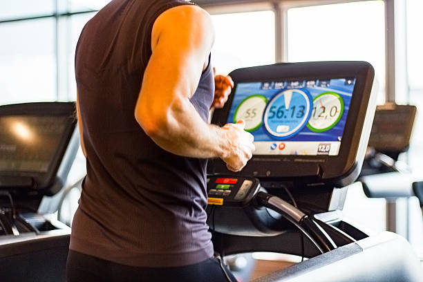 athletic runner running on treadmill in  gym - treadmill stock photos and pictures
