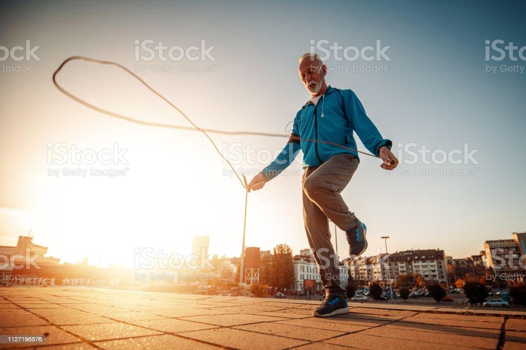 Athletic senior man running in the city stock photo