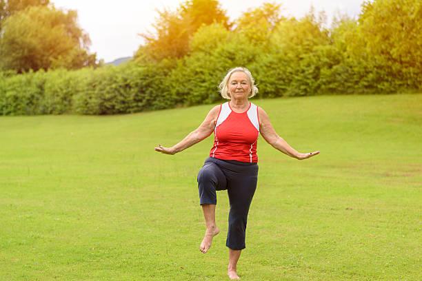 athletic senior woman performing balance exercises - granny legs stock-fotos und bilder