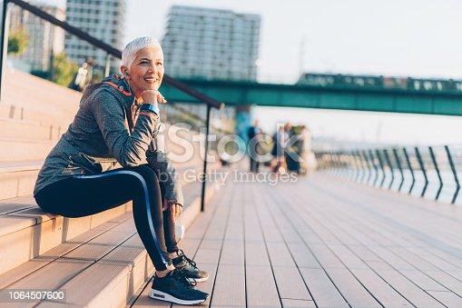 1057638814 istock photo Athletic senior woman resting 1064507600