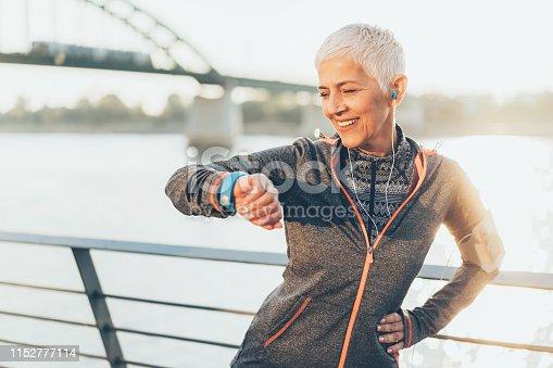 istock Athletic senior woman using smart watch 1152777114