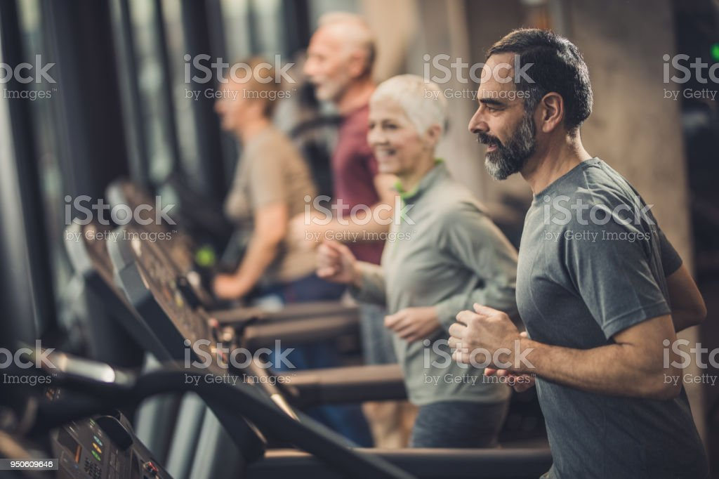 Athletic seniors running on treadmills during sports training in a health club. stock photo