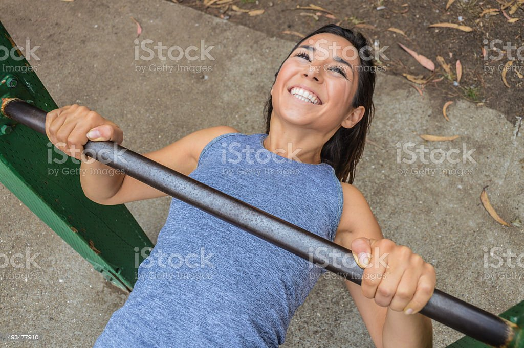 Athletic skinny woman doing pull up rows stock photo