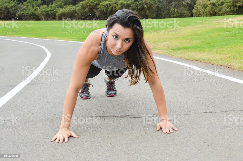 Athletic skinny woman doing push ups on track stock photo