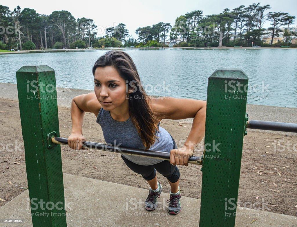 Athletic skinny woman doing push ups stock photo